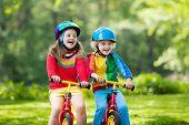 Kids Ride Balance Bike In Park poster