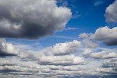 picture of cumulus-clouds  - Banks of cumulus clouds against a bright blue sky - JPG