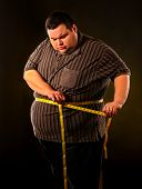 Man belly fat with tape measure weight loss around body on black background. First day of diet. Pers poster