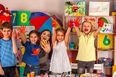 Small students with teacher finger painting in art school class. Teacher cheers children in kinderga poster