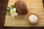Wooden spoon with fresh coconut oil and nut on table poster