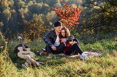 Happy Young Man Hugs His Girlfriend Tenderness And Having Rest On Picnic In The Park. Couple In Love poster