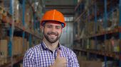 Portrait Worker In Warehouse At Work. Happy Friendly Young Man With Beard Looking At The Camera With poster