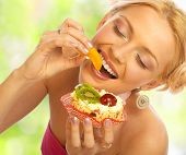 stock photo of healthy eating girl  - Pretty woman eating the cake - JPG