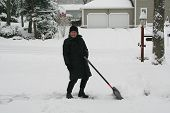 foto of snow shovel  - Senior in black shoveling driveway in winter - JPG