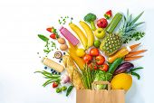 Healthy food selection. Shopping bag full of fresh vegetables and fruits isolated on white poster