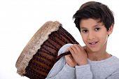 stock photo of bongo  - Little boy carrying bongo over shoulder - JPG