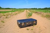 old valise on rural road