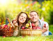stock photo of eat grass  - Happy People Eating Organic Apples in Autumn Garden - JPG