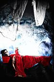 Bloodthirsty vampire woman lies in a coffin in the night cemetery. poster
