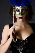 stock photo of catsuit  - Beautiful young woman holding a carnival mask wearing catsuit - JPG
