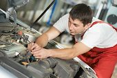 stock photo of combustion  - One young auto mechanic tighten screw with spanner during automobile car maintenance at engine repair service station - JPG