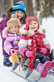 Girl pushes sledges with two younger children in winter park