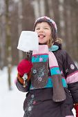 foto of eskimos  - Girl eats eskimo made of piece of snow and broken branch in winter park - JPG