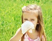 stock photo of cough  - Little girl is blowing her nose on green meadow allergy - JPG