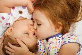 Older sister kissing baby in bed