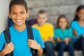 stock photo of stand up  - cheerful african american primary school boy with backpack - JPG