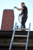 stock photo of chimney  - Chimney sweep at work on a roof with a ladder balanced against the guttering and focus to the ladder - JPG