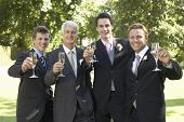 stock photo of flute  - Portrait of happy four men toasting champagne flutes at wedding day - JPG