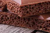 stock photo of aeration  - Aerated milk chocolate on old wooden table closeup - JPG