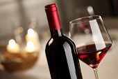 stock photo of merlot  - Red wine glass and bottle close up with restaurant on background - JPG