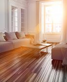 picture of lounge room  - Bright sunlight streaming into a living room interior with a parquet floor and couch through a large window with lens flare effect - JPG