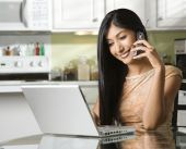 Young Woman Using Laptop And Talking On Cellphone
