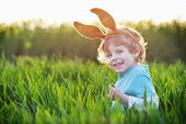 stock photo of bunny ears  - Funny boy of 3 years with Easter bunny ears playing in green grass on sunny spring day celebrating Easter holiday - JPG