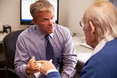 stock photo of human ear  - Doctor Showing Senior Male Patient Model Of Human Ear - JPG