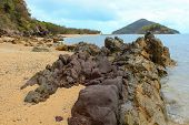 picture of deserted island  - Rocky coastline beach with islands in background - JPG