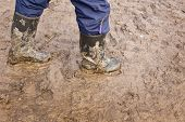 pic of wet feet  - Human legs walking with muddy rubber boots on wet silt - JPG