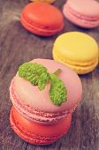 stock photo of flavor  - some appetizing macarons with different colors and flavors on a rustic wooden table - JPG