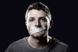 picture of freedom speech  - attractive young man with mouth and lips sealed on tape to prevent from speaking free keeping him mute and censored in freedom of speech and expression concept - JPG