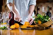 stock photo of sangria  - Man cuts oranges for making sangria for home party - JPG