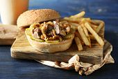 picture of burger  - Tasty burger and french fries on wooden table background  - JPG