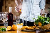stock photo of sangria  - The man squeezes orange juice in a decanter for the preparation of sangria for home party - JPG