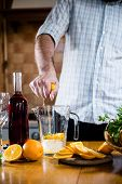 pic of sangria  - The man squeezes orange juice in a decanter for the preparation of sangria for home party - JPG
