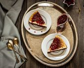 stock photo of cheesecake  - cheesecake with cherry sauce on a silver tray style a vintage on wooden table - JPG