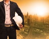 foto of land development  - engineering man and sun light behind urban construction background use for land development theme - JPG