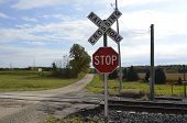 stock photo of railroad-sign  - Dusty country road with unprotected railroad tracks and farmland - JPG