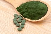 picture of green algae  - Closeup of an organic spirulina algae powder and pills in a wooden spoon - JPG