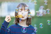 stock photo of hair blowing  - Boy with Blond Hair Blowing Bubbles Outdoor - JPG