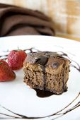 picture of chocolate fudge  - piece of chocolate brownie with chocolate sauce serve on plate - JPG