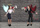 picture of angel devil  - Portrait of angel and devil girls with megaphone and copyspace between them on grey brick background - JPG