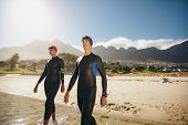 stock photo of triathlon  - Image of two young triathletes walking into the sea wearing wetsuit - JPG
