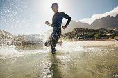 image of triathlon  - Male triathlete running into water - JPG