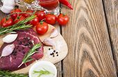 foto of beef shank  - Fresh beef steak with spices vegetables and sauce on a wooden background - JPG