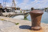 picture of bollard  - Bollard in the harbor with the background of fishing boats - JPG
