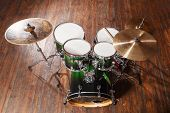 image of drum-set  - Drum set with green color stands on a brown background - JPG