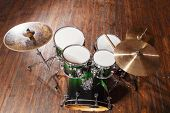 picture of drum-set  - Drum set with green color stands on a brown background - JPG
